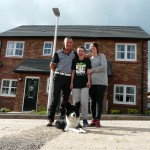 Thomas, TJ and Kim Airey outside their new home with Nell their sheepdog